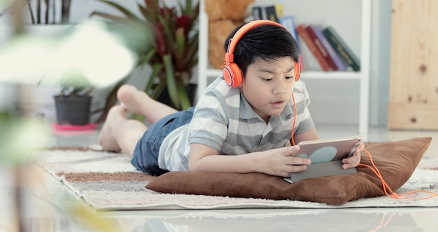 Asian boy lying and playing game on digital tablet at home