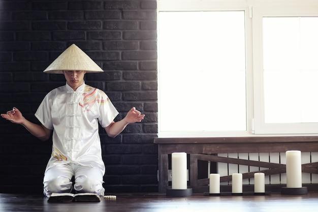 Азиатский мальчик-монах в кимоно читает старую книгу