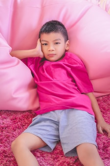 Asian boy in pink shirt is resting on a pillow