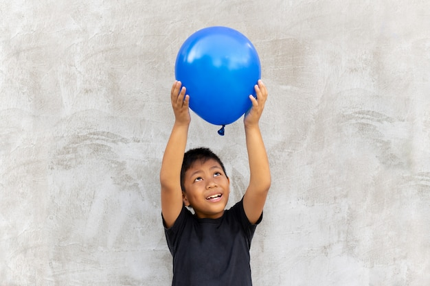 Asian boy play catches balloon on grey background.