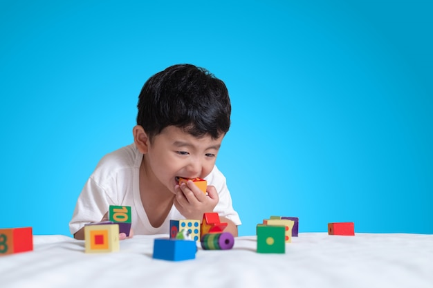 Asian boy play square block puzzle toy on the bed