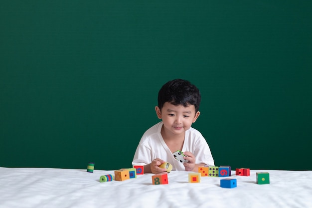 Asian boy play toy or square block puzzle on green chalkboard