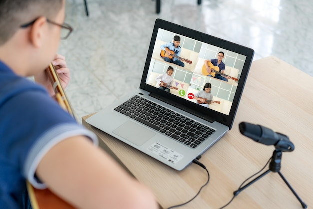 Asian boy playing acoustic guitar virtual happy hour meeting for play music online together
