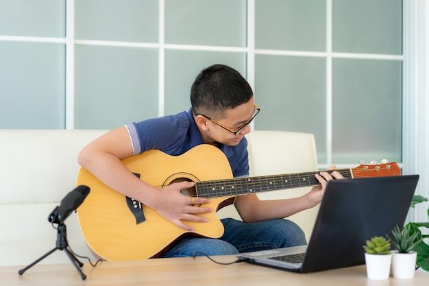 Asian boy playing acoustic guitar and watching online course on laptop