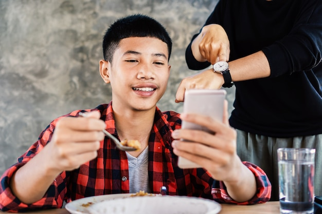 Asian boy playing game while eating dinner