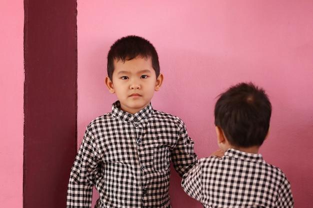 분홍색 콘크리트 벽에서 형제와 노는 아시아 소년과 복사 공간, 형제 자매와 아이들의 귀여움의 개념.