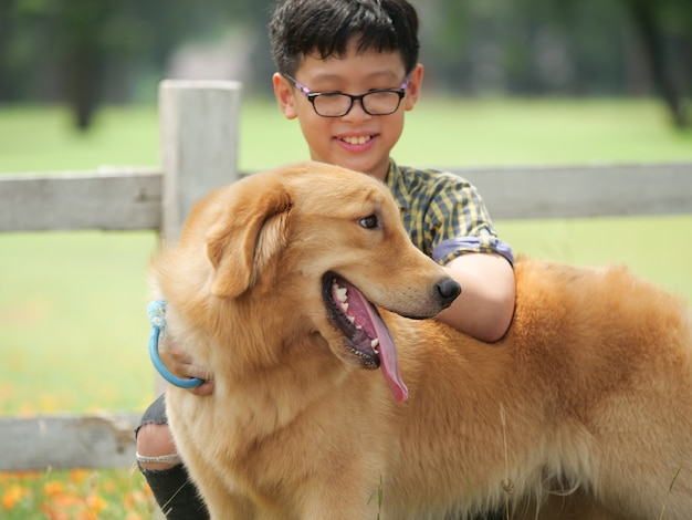 Asian boy playing with puppy dog golden retreiver in park