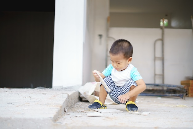 Asian boy playing with stuff at house construction site