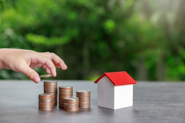 Asian boy putting money to coin stack with house model on green.