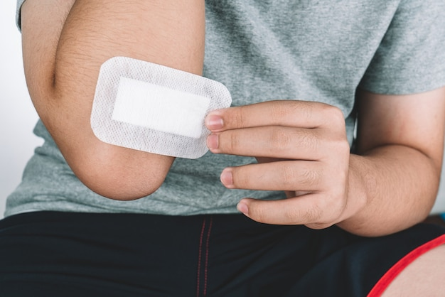 Asian boy putting sticking plaster on injured elbow skin by himself. first aid for cuts and wounds.