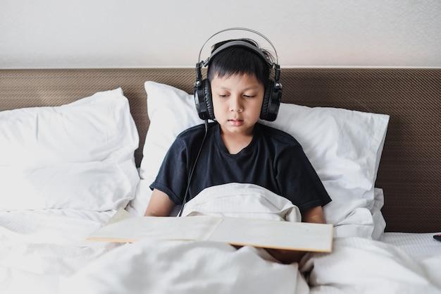 ヘッドフォンで音楽を聴きながらベッドで本を読んでいるアジアの少年