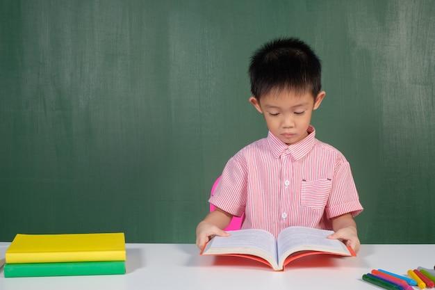 Asian boy reading a book in chalk board room