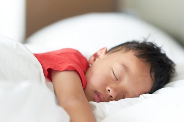 アジアの少年の睡眠または快適な枕と深い睡眠のベッドで昼寝
