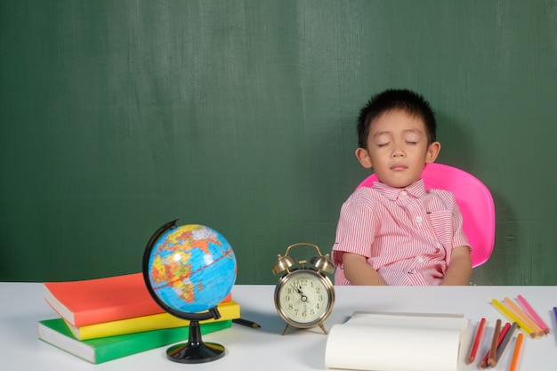 Asian boy sleeping in chalk board room
