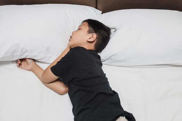 ベッドで寝ているアジアの少年