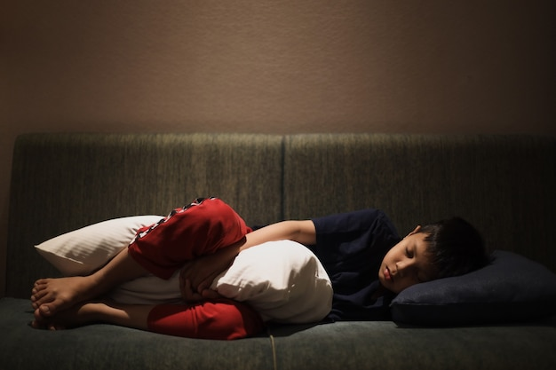 枕を抱きしめながらソファで寝ているアジアの少年