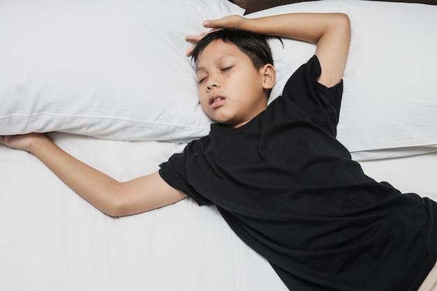 ベッドでぐっすり眠っているアジアの少年