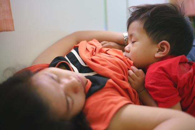 Asian boy sleeping while breastfeeding