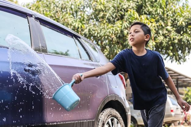 Азиатский мальчик брызгает водой ковшом, чтобы намочить машину