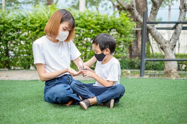 Азиатский мальчик распыляет спирт на руку матери, чтобы мыть руки. изображение антивируса здоровья.