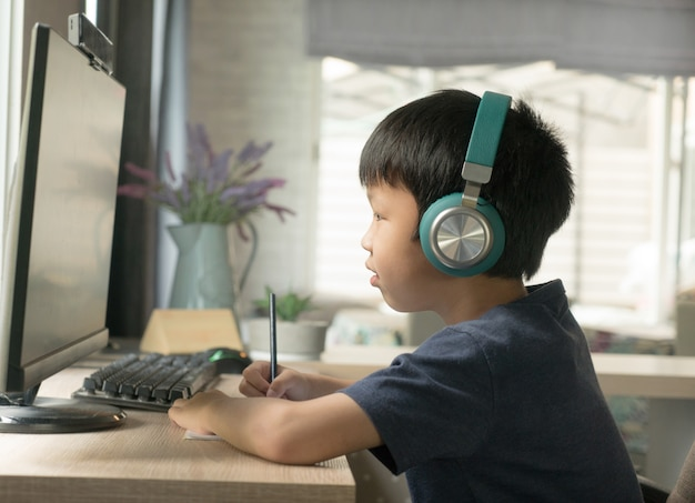 Asian boy student in headphone paying attention on online learning via computer in living room at home, home schooling concept.