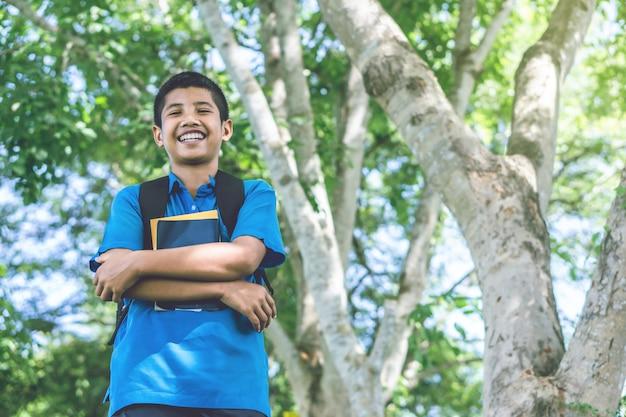 公園で笑いながら本を持っているアジアの少年学生