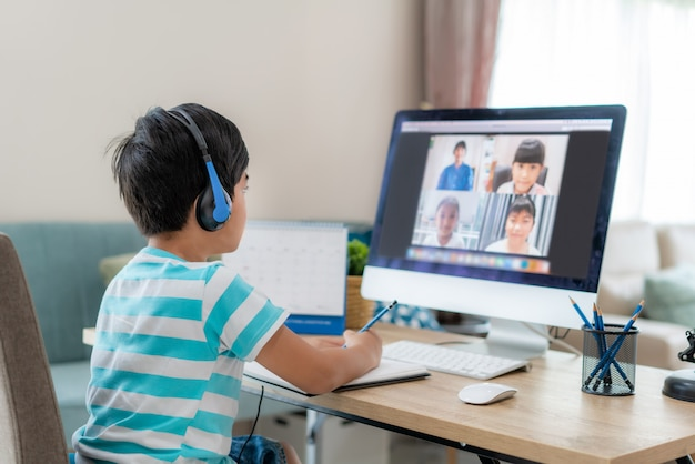 Asian boy student video conference e-learning with teacher and classmates on computer