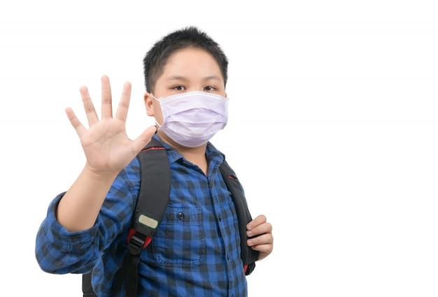 アジアの男子生徒が学校に行く前にマスクを着用し、さようならを振る