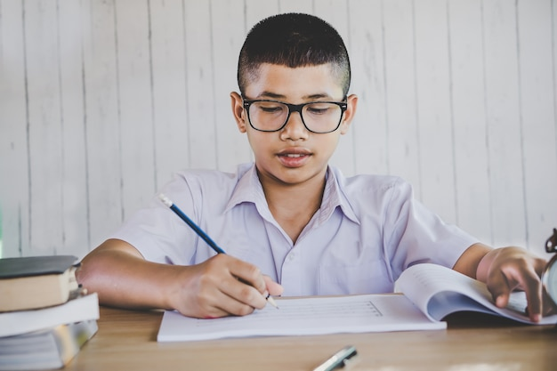 Asian boy student writing in a classroom