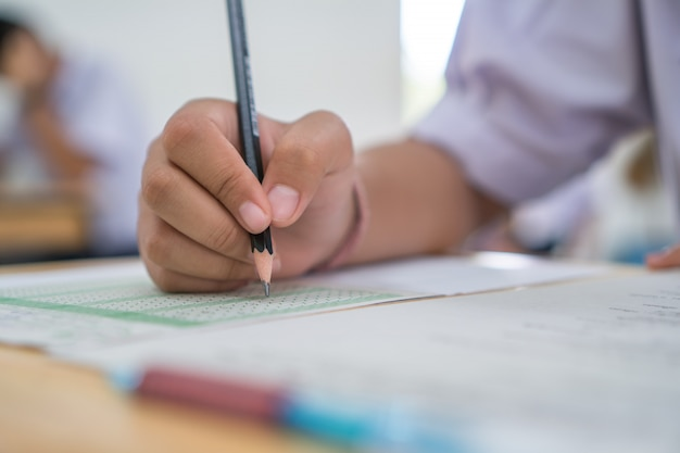 Asian boy students taking exams, writing examination room with undergraduate students