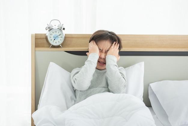 침실에서 알람 시계와 함께 수면 부족으로 고통받는 아시아 소년