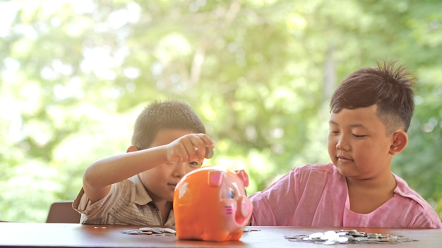 Asian boy two people happy smile fun putting coins in a piggy bank