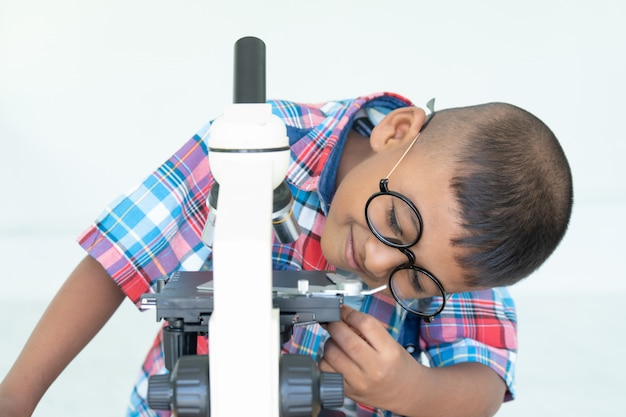 Asian boy use microscope in lab for research