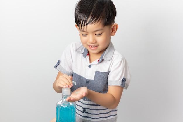アルコール消毒ゲルを使用して手を洗浄するアジアの少年。コロナウイルス消毒