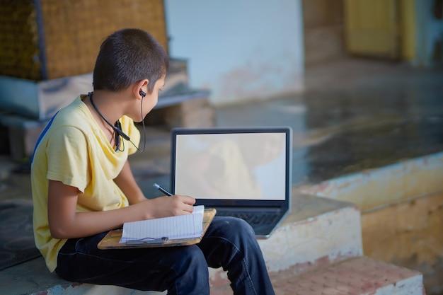 自宅検疫中にオンライン学習ホームスクーリングのためにラップトップコンピューターを使用しているアジアの少年。ホームスクーリング、オンライン学習、家庭検疫、オンライン学習、コロナウイルスまたは教育技術の概念