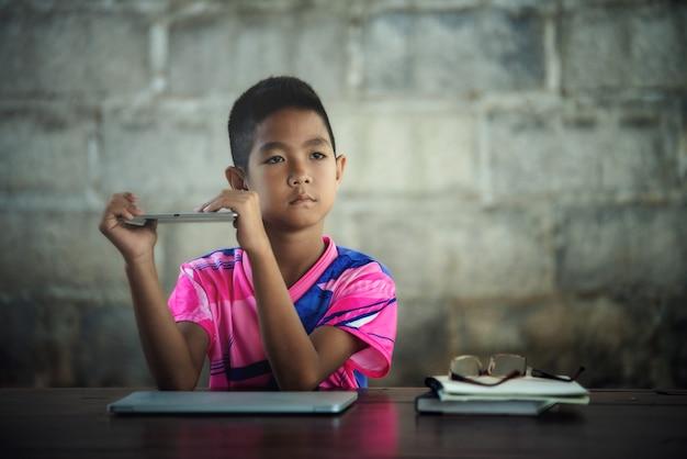 아시아 판 남자 아이 랩탑 형 사용하여 테이블
