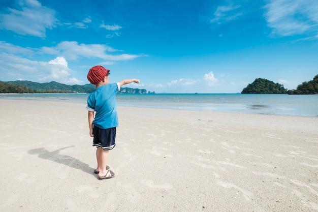 ビーチで歩くアジアの少年海と青空