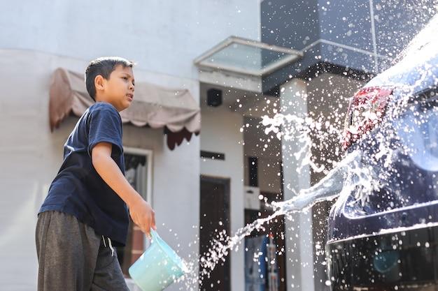 Азиатский мальчик моет машину, промывая машину с помощью ковша