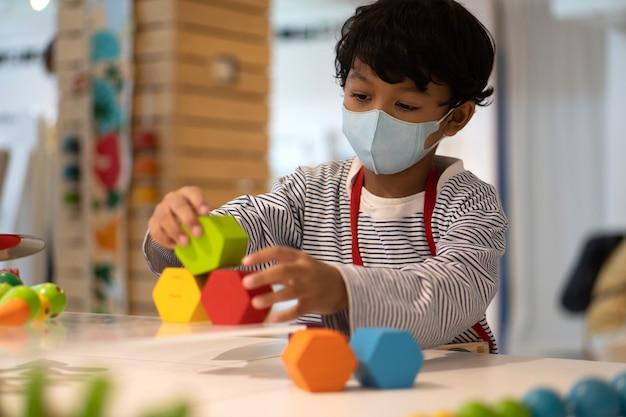 アジアの少年は、コロナウイルス2019(covid-19)を防ぐためにフェイスマスクを着用し、学校でおもちゃで遊んでいます。