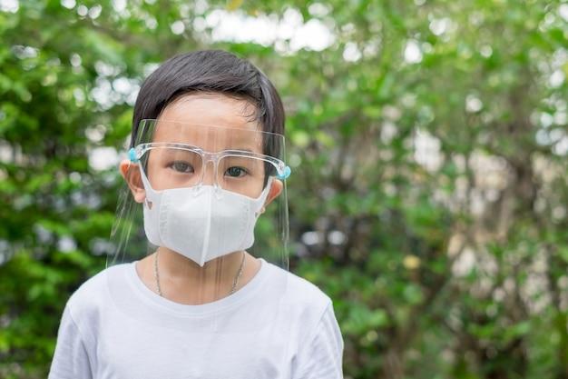 아시아 소년 집 정원에서 마스크와 얼굴 방패를 착용