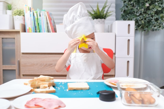 Asian boy wearing a chef hat and apron while cooking