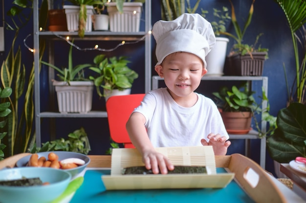 Asian boy wearing chef hat and apron while cooking