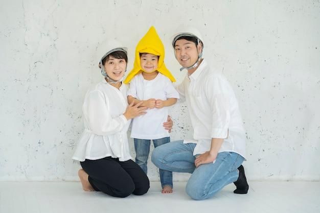 防災フードをかぶったアジアの少年とヘルメットをかぶった両親