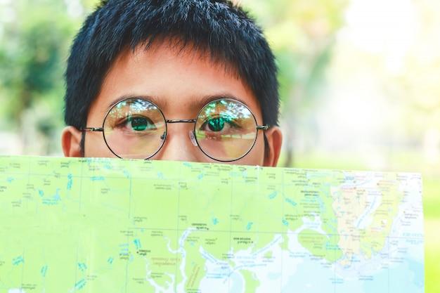 Азиатский мальчик в очках, держа бумагу, карта мира закрыла лицо