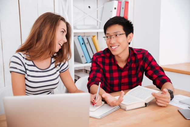 Asian boy wearing glasses and dressed in shirt in a cage and caucasian woman dressed in t-shirt in a strip print working together for project at classroom