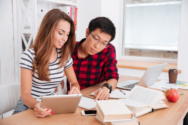 Asian boy wearing glasses and dressed in shirt in a cage and girl dressed in t-shirt in a strip print working together for project while sitting at classroom