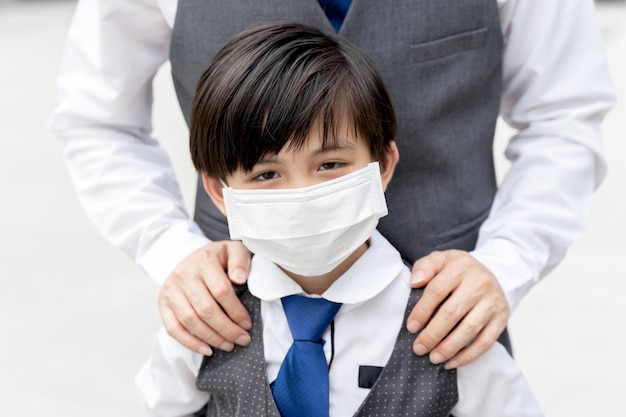 Asian boy wearing protective face mask for protection during the quarantine coronavirus covid 19 outbreak