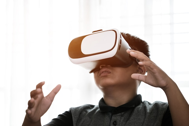 Asian boy wearing vr / virtual reality goggles interaction headset in home studio, enjoying and learning study new digital simulation sci and game, futuristic innovation device concept