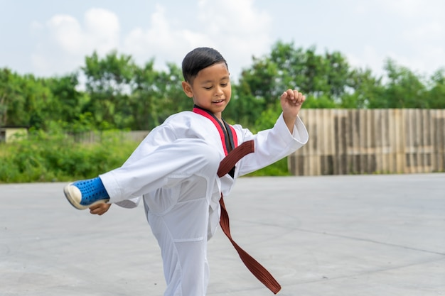 Asian boy wearing white taekwondo suit acting kick to battle, sport concept