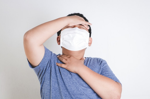 An asian boy wears a mask, covering his mouth and nose, preventing coronavirus.